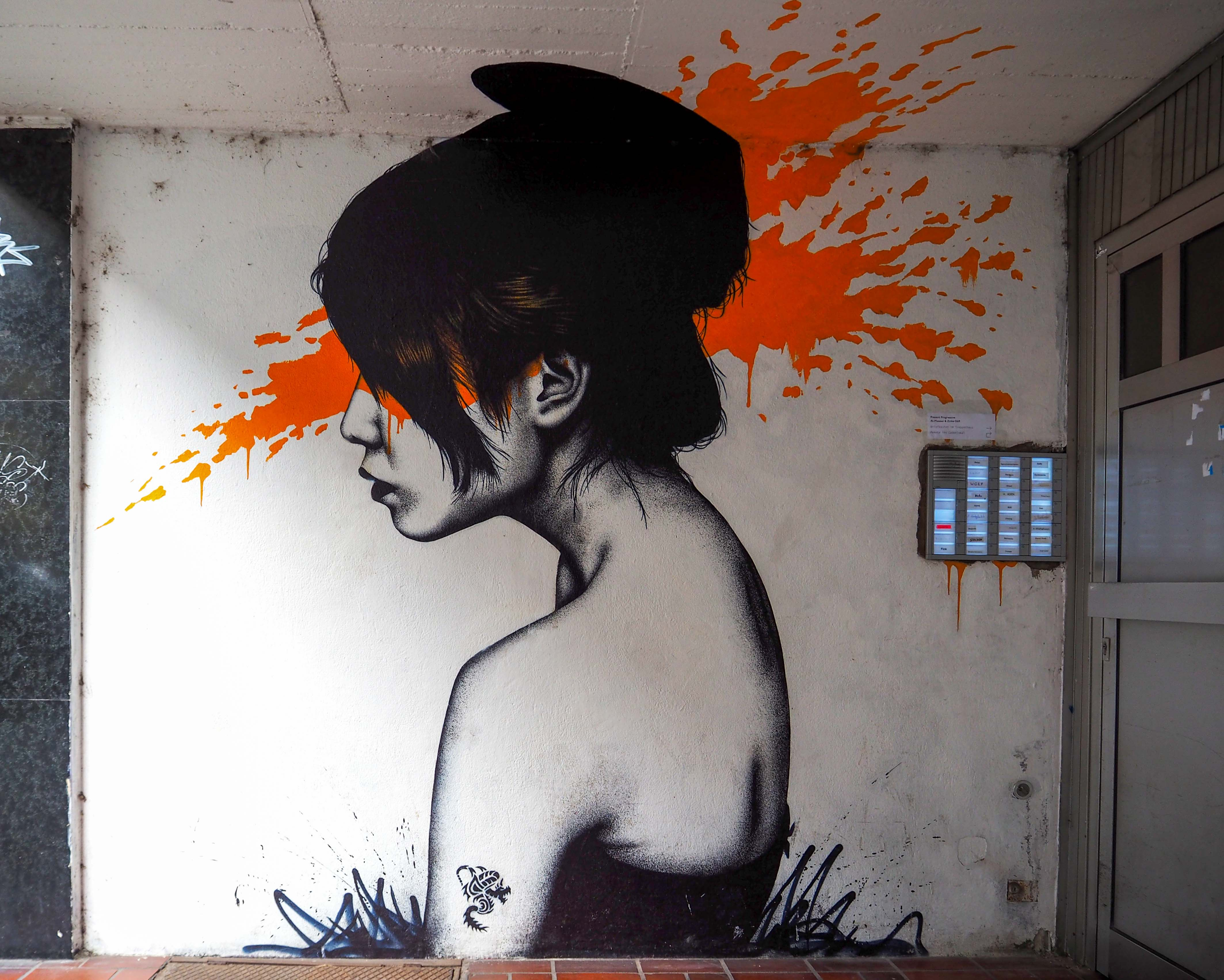 FinDac malte sein Moonchild, eine asiatisch wirkende junge Frau mit orangem Farbhintergrund in einem Hauseingang