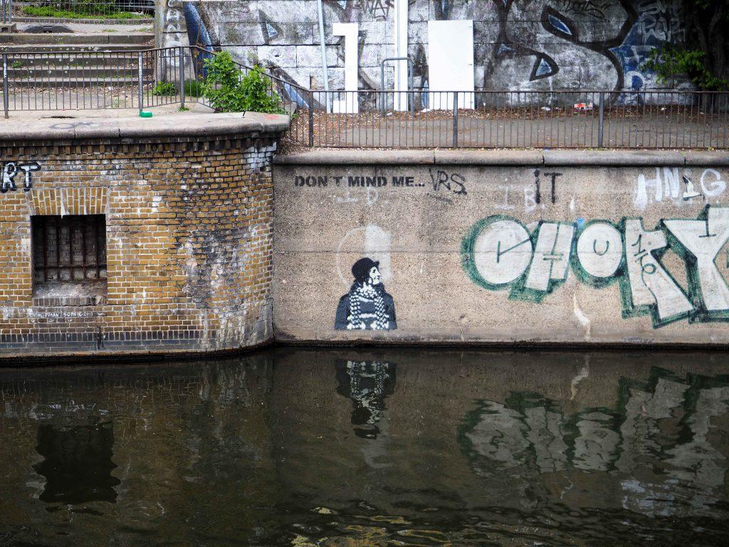 an der Kaimauer eines Flusses klebt ein past up mit einem Mann mit Hut