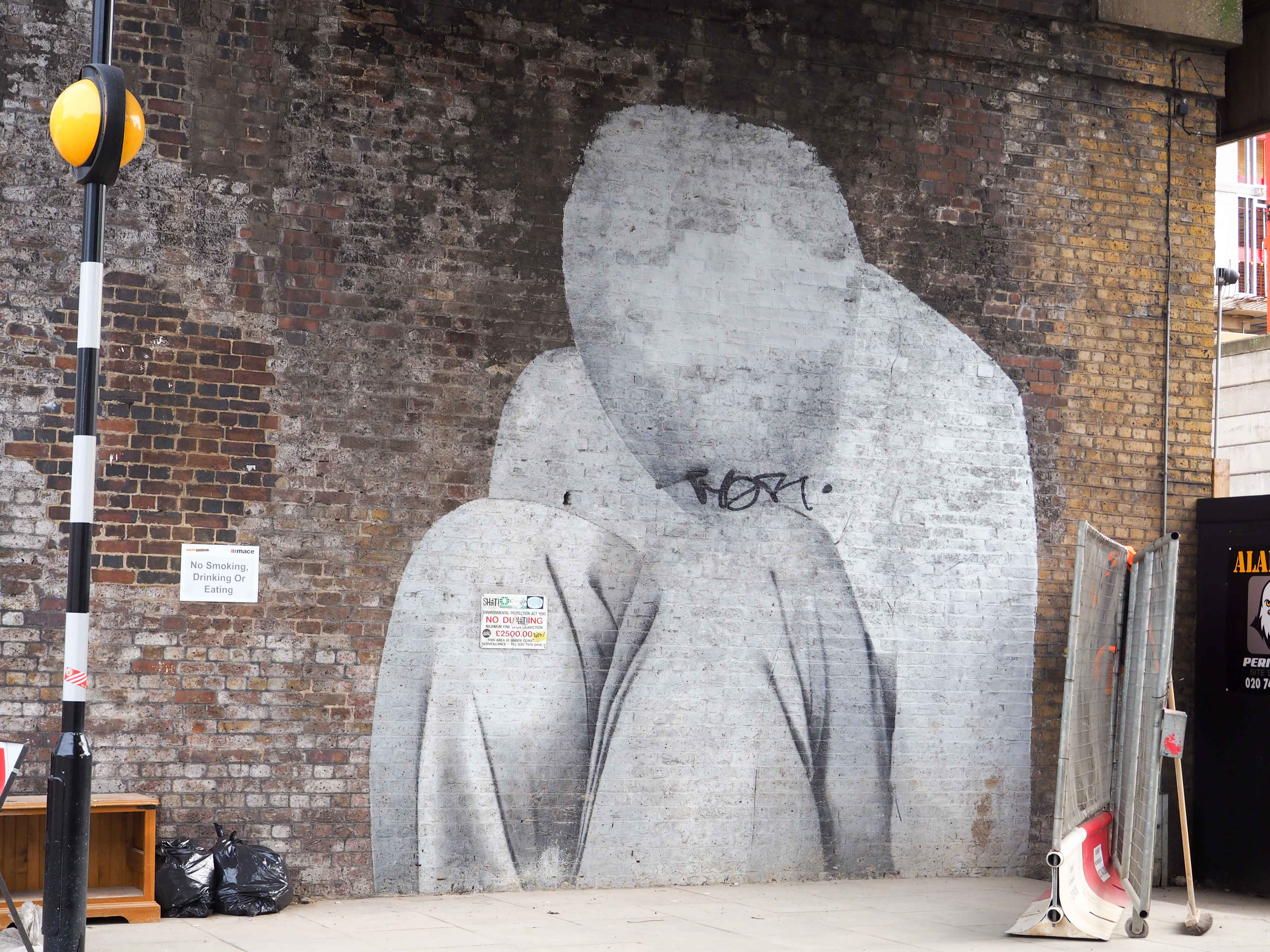 unbekannter Künstler stellt hockenden Menschen mit verdecktem Kopf auf einem Brückenpfeiler dar