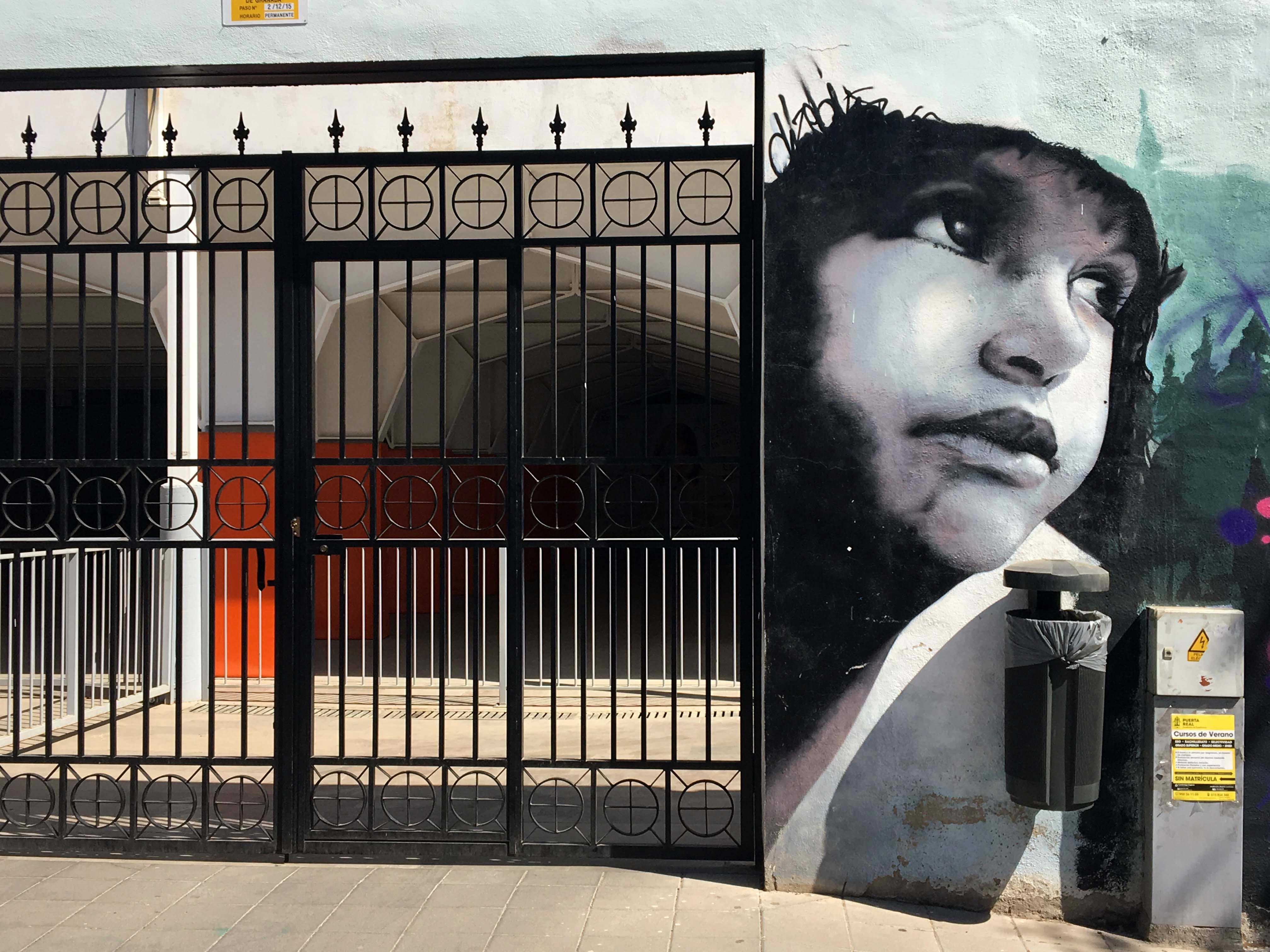 rechte Seite neben einem Tor Mural von El Niño de las Pinturas dass ein Kind zeigt