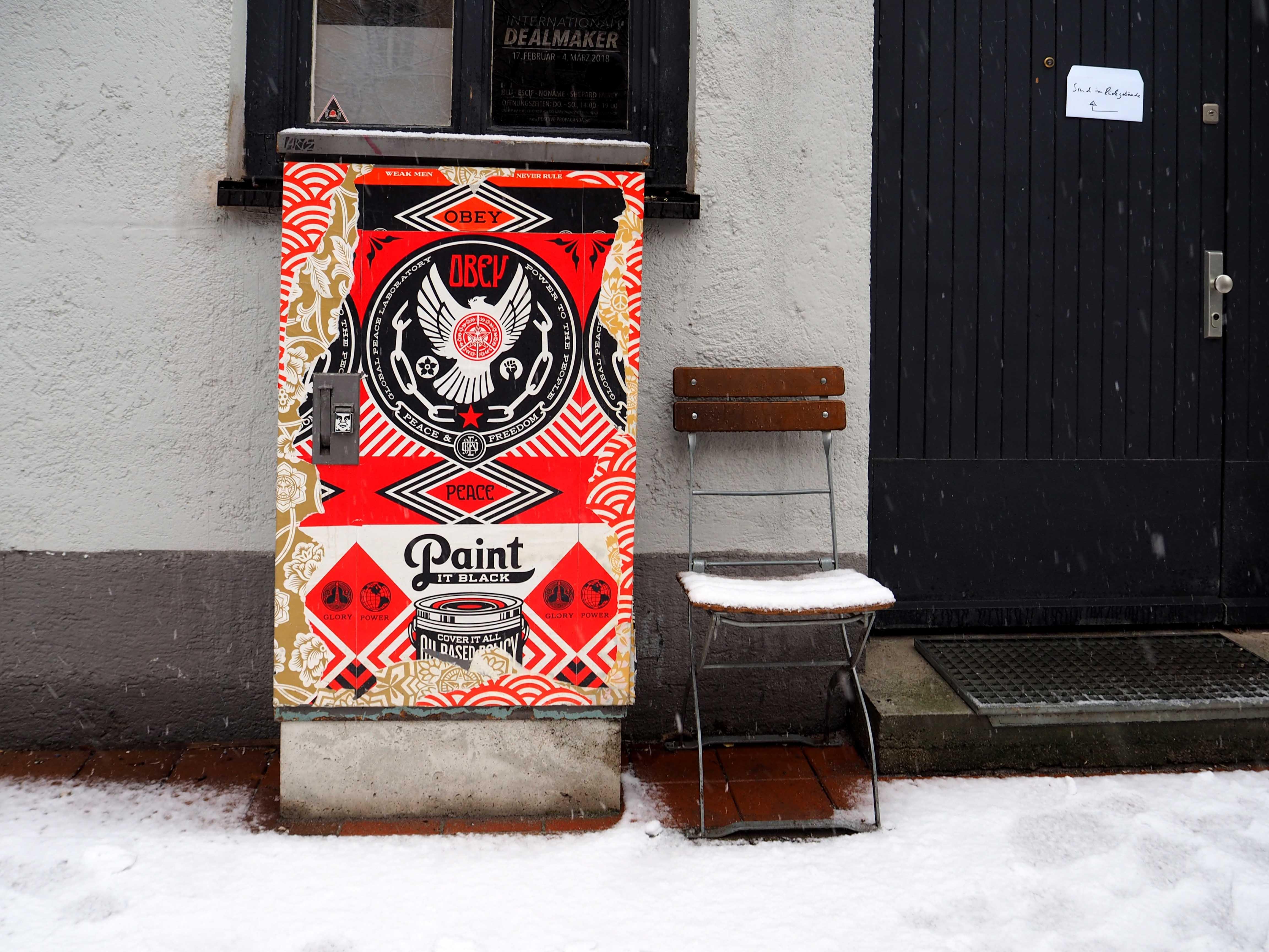 vor einem Eingang steht ein Stromkasten, der von Shepard Fairey gestaltet ist