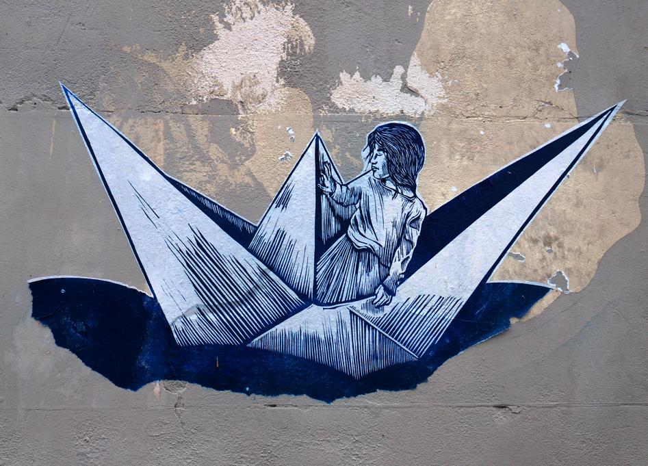 Kind auf Papierschiffchen
