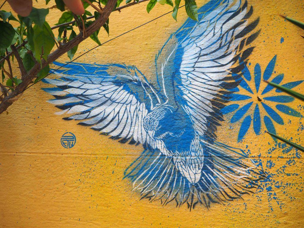 blauer Vogel auf gelbem Grund