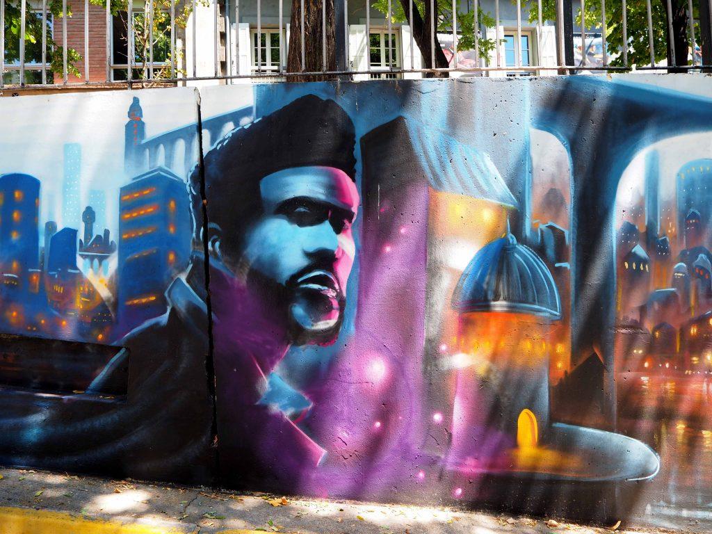 Graffiti von Mann vor Stadtansicht