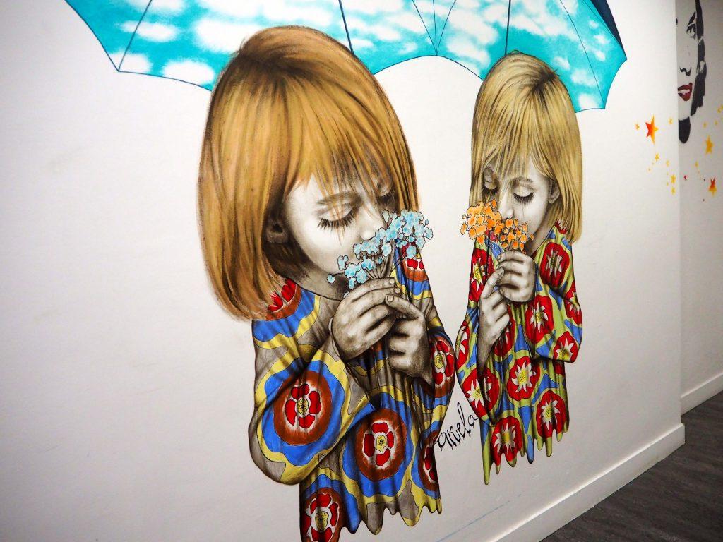 zwei Mädchen riechen an Blumen