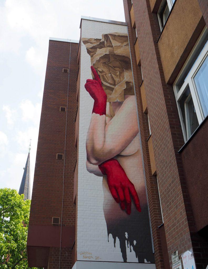 nackte Frau mit roten Handschuhen und Papiertüte über dem Kopf