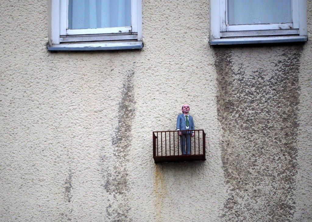 Miniaturmann auf kleinem Balkon an Hauswand